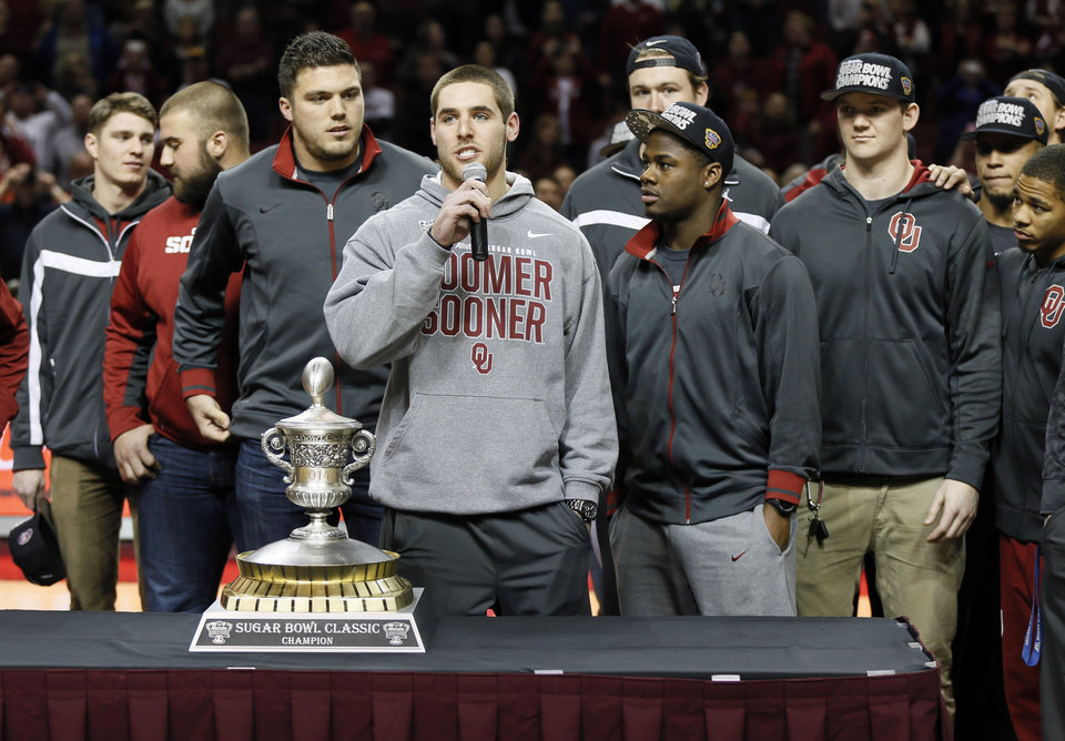 Photo - Surrounded by his teammates, OU football player Trevor Knight addresses the crowd at halftime as he stands next to the Sugar Bowl trophy during an NCAA men's college basketball game between Baylor and the University of Oklahoma (OU) at Lloyd Noble Center in Norman, Okla., Saturday, Feb. 8, 2014. Photo by Nate Billings, The Oklahoman