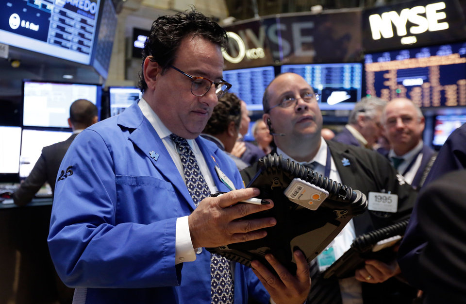Photo - Peter Costa works with fellow traders on the floor of the New York Stock Exchange, Tuesday, April 22, 2014. Stock futures edged higher as more companies reported first quarter earnings. (AP Photo/Richard Drew)