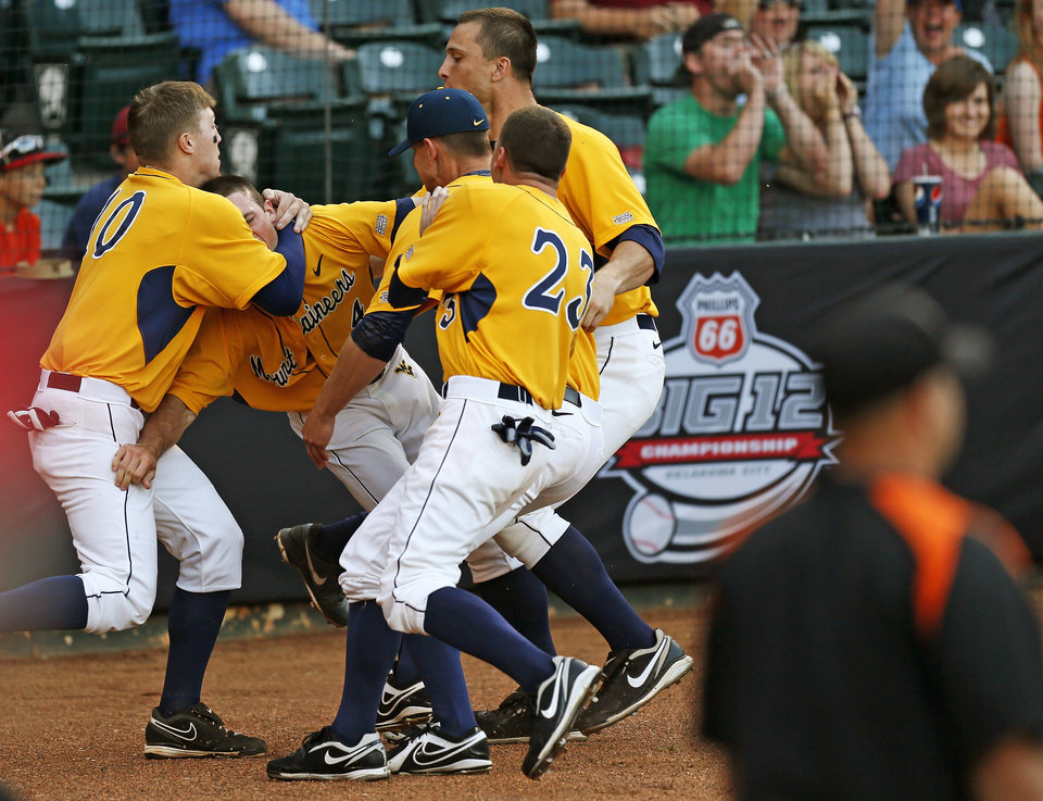 Photo - West Virginia players celebrate with Bobby Boyd (4), second from left, after he scored the winning run in the tenth inning during an NCAA baseball game between Oklahoma State and West Virginia in the Big 12 Baseball Championship tournament at the Chickasaw Bricktown Ballpark in Oklahoma City, Saturday, May 25, 2013. WVU beat OSU 6-5 in ten innings. Photo by Nate Billings, The Oklahoman