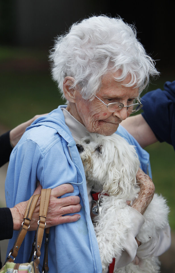 Photo - Unidentified woman and her dog that were rescued by boat from her home in  The Valley addition in Edmond, Monday,  June 14, 2010.     Photo by David McDaniel, The Oklahoman
