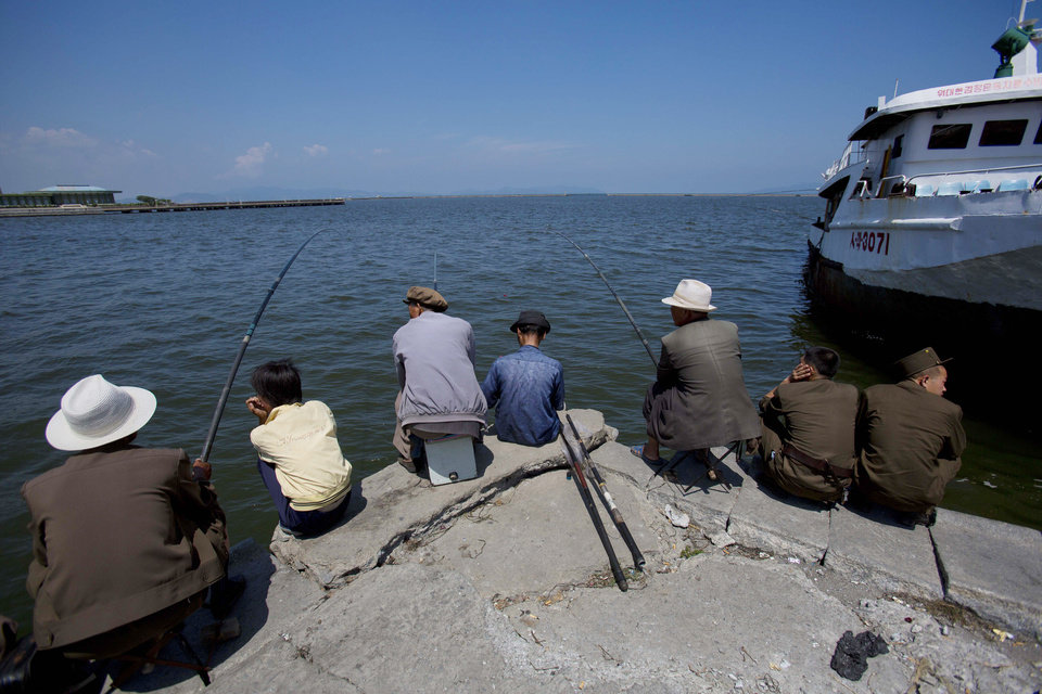 Photo - FILE - In this Aug. 9, 2012 file photo, people fish at the port in Wonsan, North Korea. Wonsan, a sleepy port on North Korea's east coast, is gearing up for a busy summer - and, if talks with Japan go as North Korea hopes, maybe a return to livelier days. Opening the door just a crack to better relations, Pyongyang has set up a committee to reinvestigate the fates of a dozen Japanese citizens who Tokyo suspects were abducted by North Korean agents in the 1970s and 80s. In return, Prime Minister Shinzo Abe is considering easing a broad array of unilateral sanctions that have shut down virtually all trade and most contact between the countries. (AP Photo/David Guttenfelder, File)