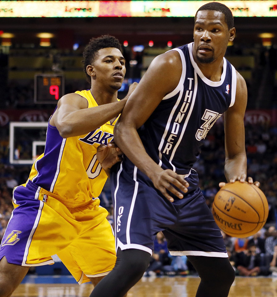 Photo - Oklahoma City's Kevin Durant (35) works against LA's Nick Young (0) during an NBA basketball game between the Los Angeles Lakers and the Oklahoma City Thunder at Chesapeake Energy Arena in Oklahoma City, Friday, Dec. 13, 2013. Photo by Nate Billings, The Oklahoman