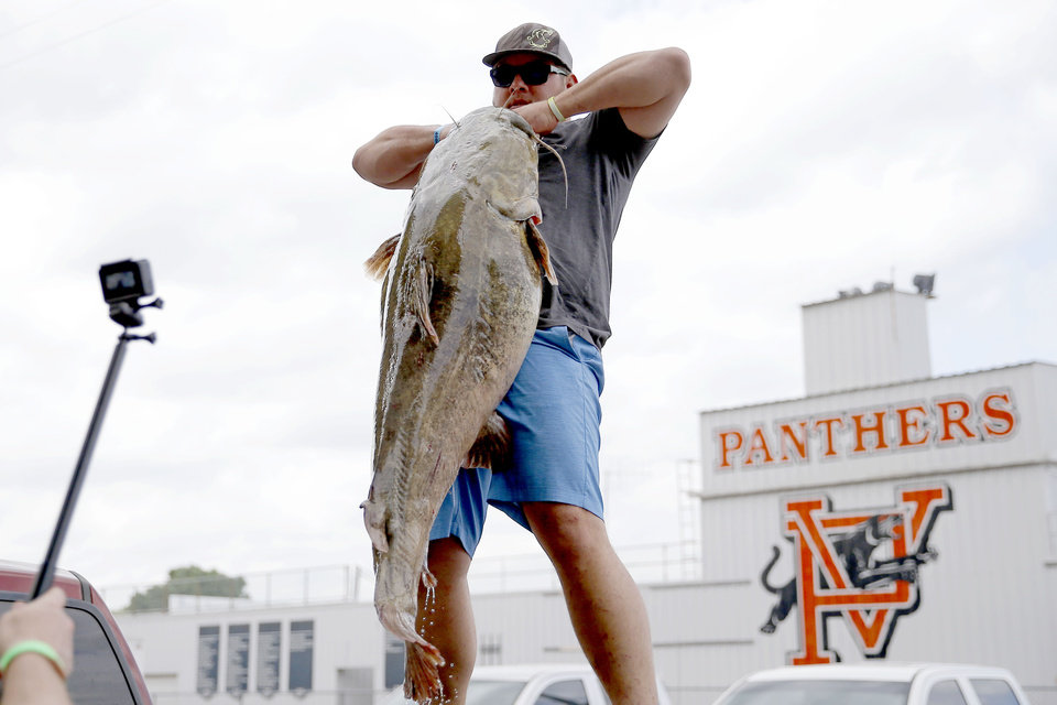 Photo - Nate Williams of Shawnee, Okla., poses for a photo with his 85.05 pound catfish during the Okie Noodling Tournament and Festival at Wacker Park in Pauls Valley, Okla., Saturday, June 15, 2019. [Bryan Terry/The Oklahoman]