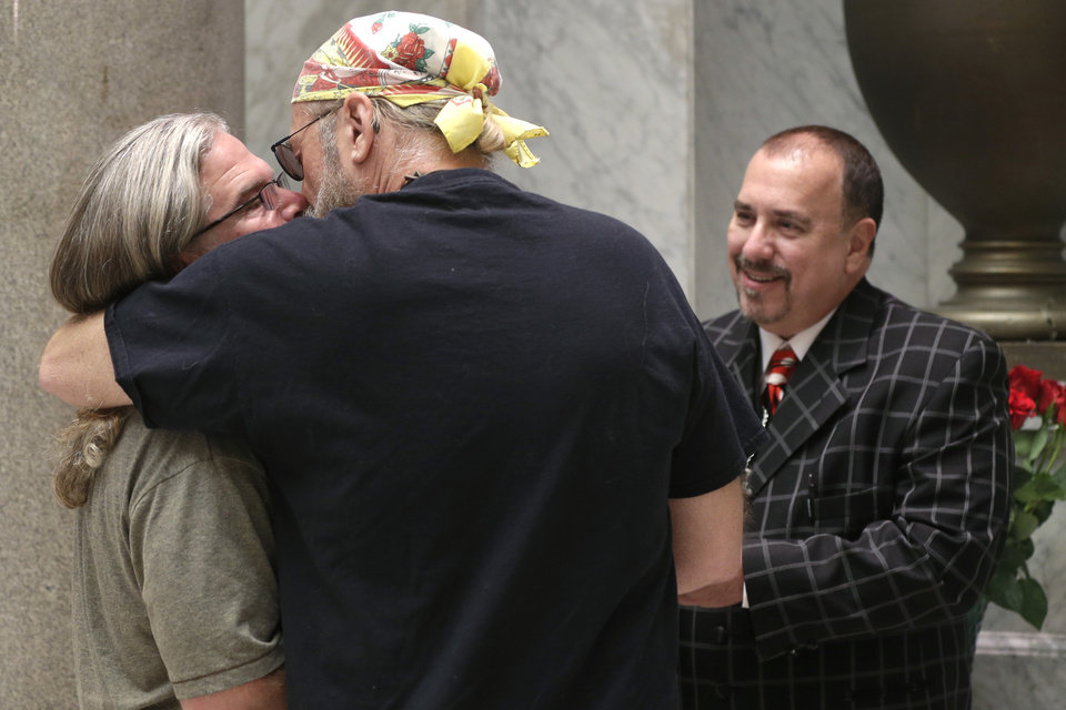 Photo - Pastor Randy Eddy-McCain, right, concludes a wedding ceremony at the Pulaski County Courthouse in Little Rock, Ark., for a same-sex couple who did not wish their names used Thursday, May 15, 2014. Marriage licenses were issued to same-sex couples in the county Thursday. (AP Photo/Danny Johnston)