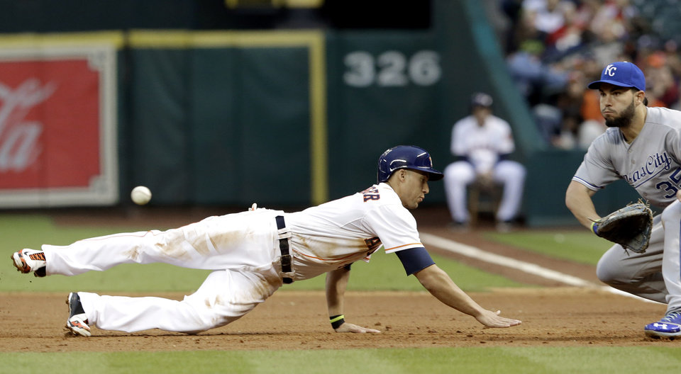 Photo - Houston Astros' George Springer, left, dives back to first base ahead of the ball as Kansas City Royals first baseman Eric Hosmer (35) waits for the throw in the first inning of a baseball game on Thursday, April 17, 2014, in Houston. (AP Photo/Pat Sullivan)
