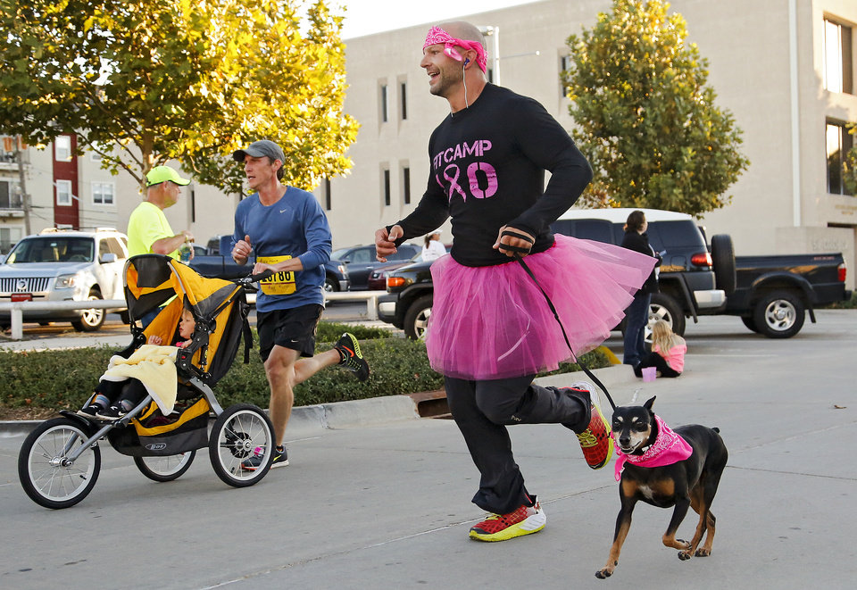 Photo -  Shawn Busby runs with his dog Jackson during the 23rd annual Oklahoma City Susan G. Komen Race for the Cure at the Civic Center in Oklahoma City on Saturday. [Photo by Chris Landsberger, The Oklahoman]