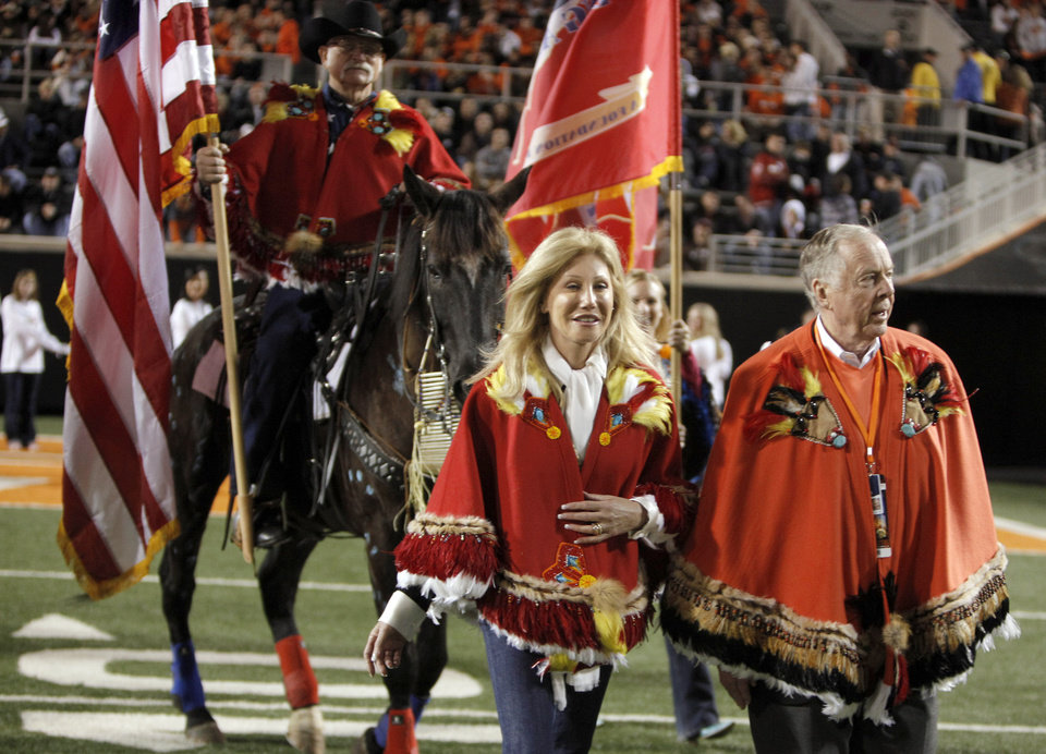 Photo - Madeleine and Boone Pickens lead Mutstang horses onto the field during halftime of the  college football game between Oklahoma State University (OSU) and the University of Colorado (CU) at Boone Pickens Stadium in Stillwater, Okla., Thursday, Nov. 19, 2009. Photo by Sarah Phipps, The Oklahoman