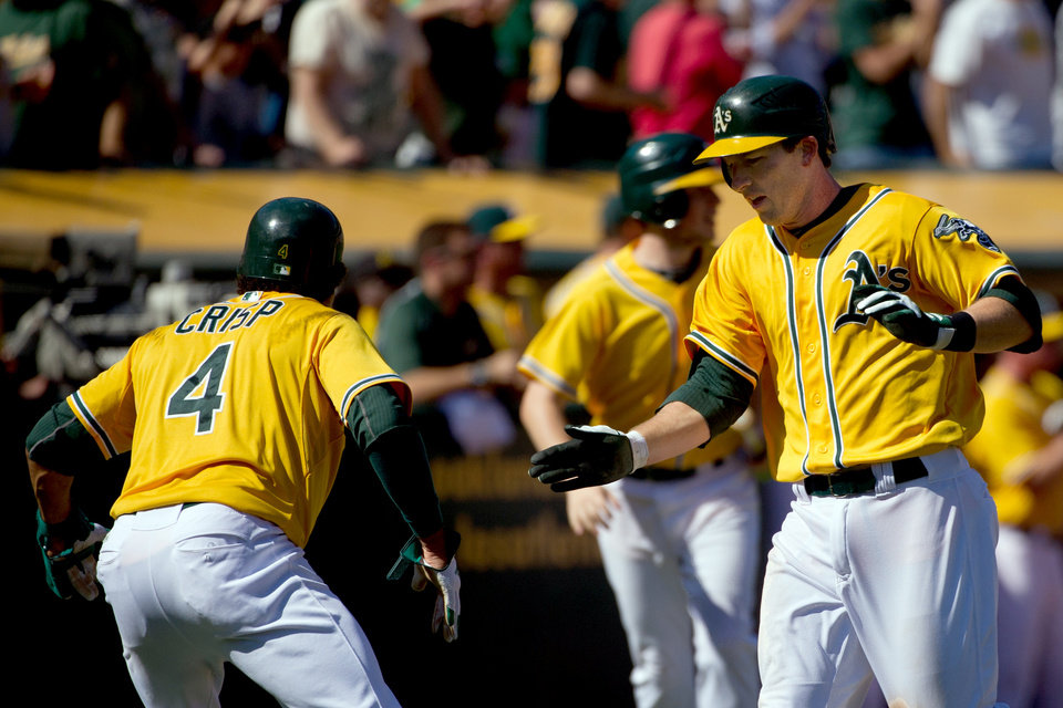 Photo -   Oakland Athletics' Stephen Drew, right, and Coco Crisp (4) celebrate after scoring on an error by Texas Rangers center fielder Josh Hamilton during the fourth inning of their baseball game, Wednesday, Oct. 3, 2012, in Oakland, Calif. The Athletics won 12-5 to clinch the American League West. (AP Photo/The Sacramento Bee, Jose Luis Villegas) MAGS OUT; LOCAL TV OUT (KCRA3, KXTV10, KOVR13, KUVS19, KMAZ31, KTXL40); MANDATORY CREDIT