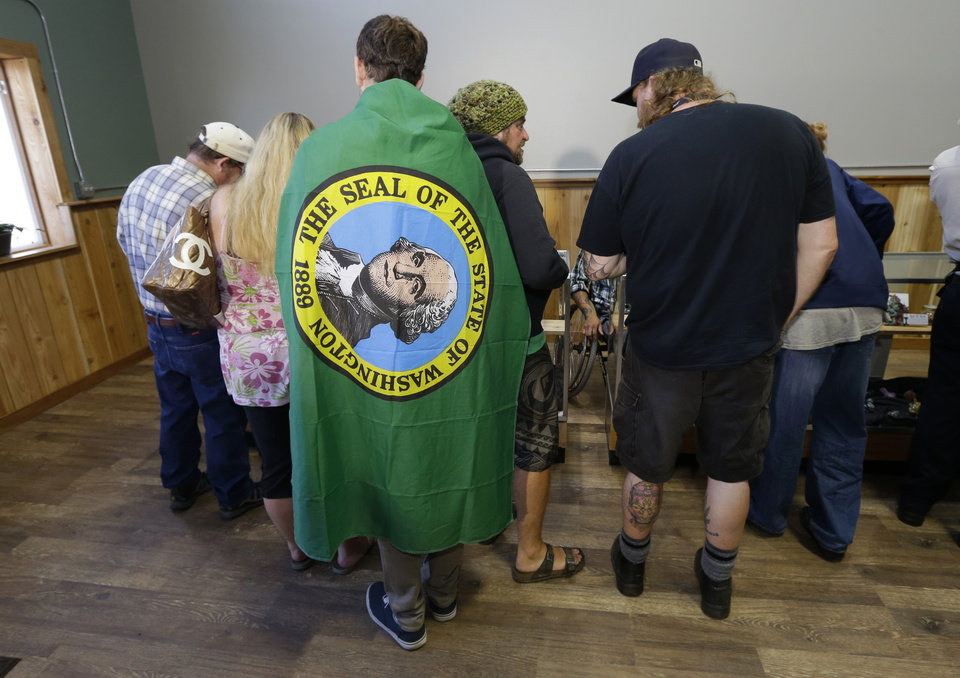 Photo - Brian Travino, a student at Western Washington University wears a Washington state flag, as he waits with other customers to purchase recreational marijuana at Top Shelf Cannabis, Tuesday, July 8, 2014, in Bellingham, Wash., in the first half-hour of legal sales in the state. (AP Photo/Ted S. Warren)