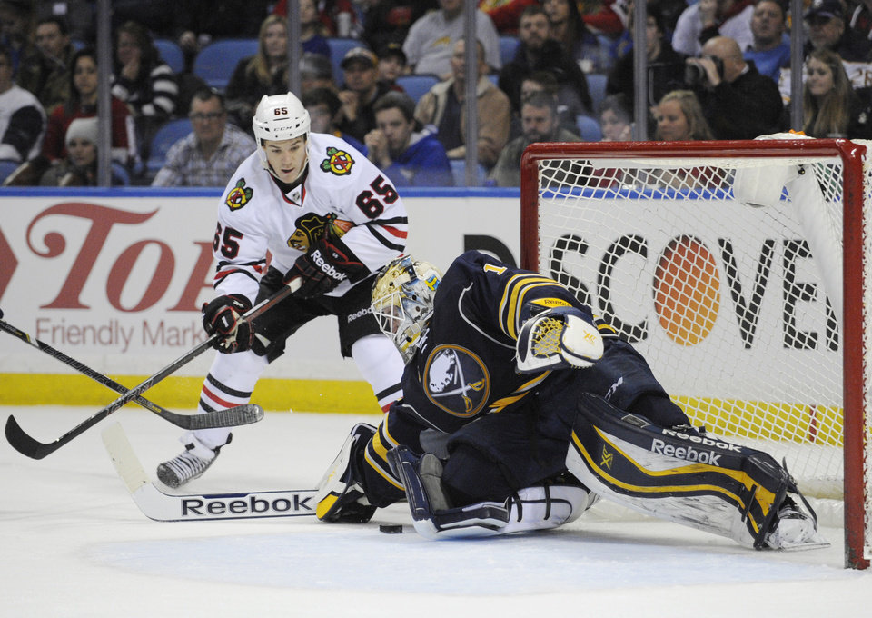 Photo - Chicago Black Hawks center Andrew Shaw (65) battles for a rebound as Buffalo Sabres goaltender Jhonas Enroth (1) makes  a save during the second period of an NHL hockey game in Buffalo, N.Y., Sunday, March 9,  2014. (AP Photo/Gary Wiepert)