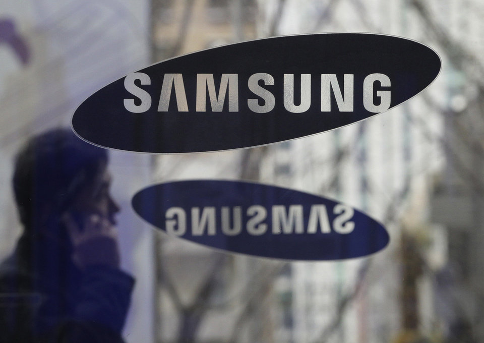 Photo - File - In this Dec. 12, 2013 file photo, a man passes by the Samsung Electronics Co. logos at its headquarters in Seoul, South Korea. Opening statements are underway in the latest patent fight over mobile devices between Apple and Samsung, the world's largest cellphone manufacturers. An Apple lawyer told jurors in San Jose, Calif., on Tuesday April 1, 2014, that Samsung quickly recognized that the iPhone was going to be a big seller when it first went on the market, and the South Korean company didn't have a product that could compete. (AP Photo/Ahn Young-joon, File)
