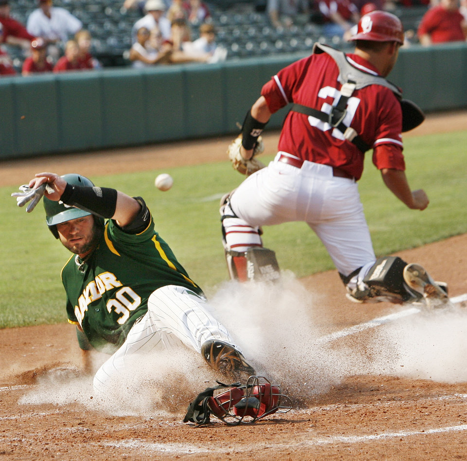 Photo - Baylor's Josh Ludy (30) slides home to score past OU's Tanner Toal (31) in the fourth inning during a Big 12 Baseball Championship tournament game between the Oklahoma Sooners and Baylor Bears at the Chickasaw Bricktown Ballpark in Oklahoma City,Thursday, May 24, 2012. OU won, 3-2. Photo by Nate Billings, The Oklahoman