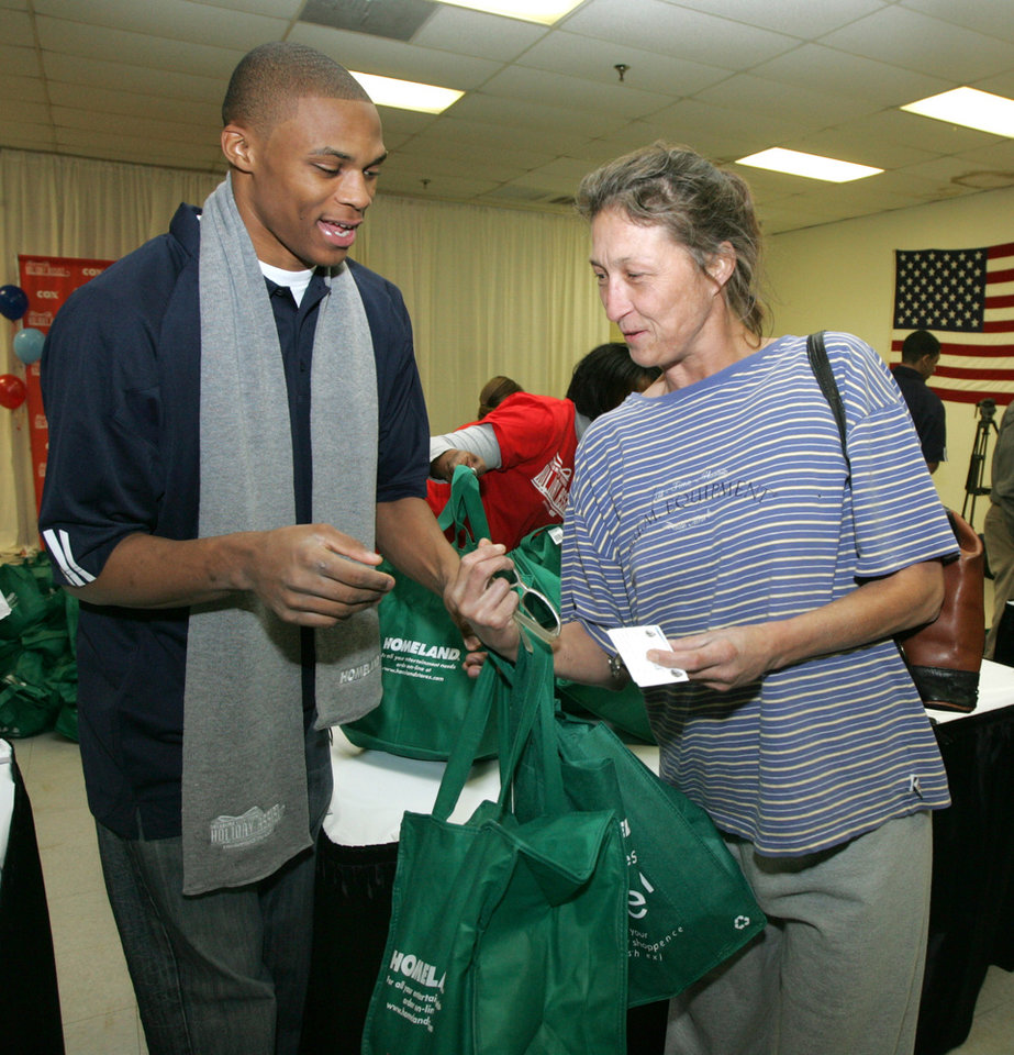 Photo - THANKSGIVING / CHARITY / TURKEYS / DONATE / DONATIONS: Oklahoma City Thunder NBA basketball player Russell Westbrook gives a bag of food to Patty Estep at the Presbyterian Urban Mission in Oklahoma City, Okla. November 20, 2008.  BY STEVE GOOCH, THE  OKLAHOMAN. ORG XMIT: KOD