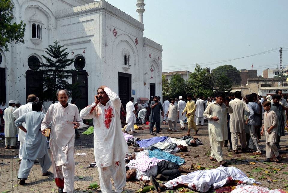 EDS NOT: GRAPHIC CONTENT - People gather next to victims of a suicide attack on a church in Peshawar, Pakistan, Sunday, Sept. 22, 2013. A suicide bomb attack on a historic church in northwestern Pakistan killed scores of people Sunday, officials said, in one of the worst assaults on the country's Christian minority in years. (AP Photo/Mohammad Sajjad)