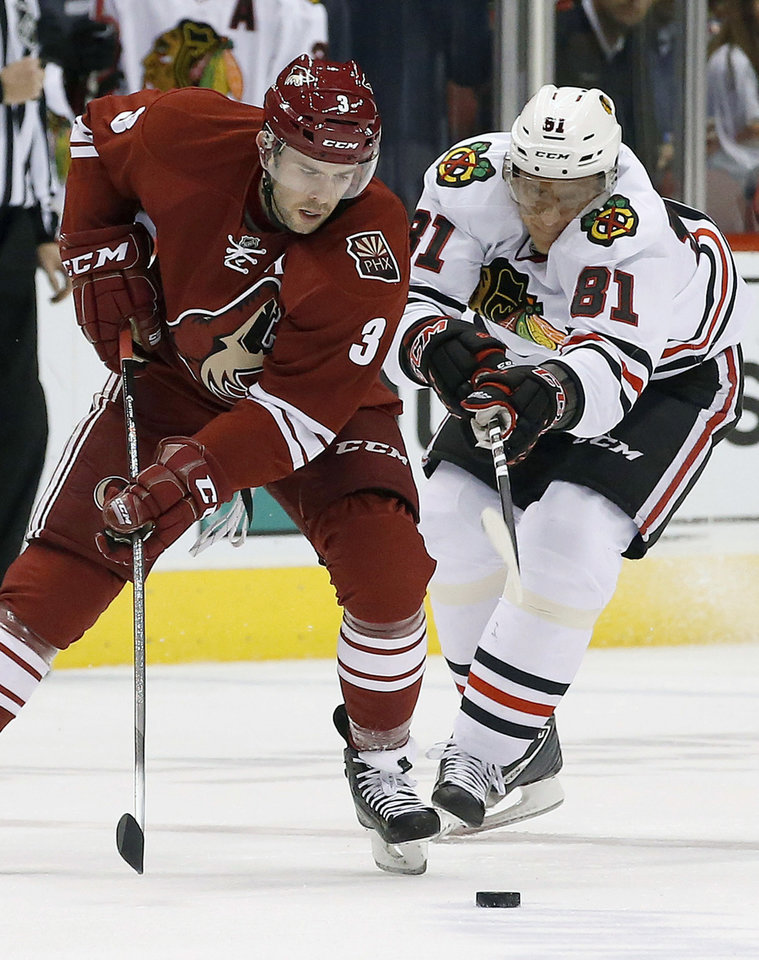 Phoenix Coyotes\' Keith Yandle (3) tries to keep the puck away from Chicago Blackhawks\' Marian Hossa (81) during the first period in an NHL hockey game, Friday Feb. 7, 2014, in Glendale, Ariz. (AP Photo/Ross D. Franklin)