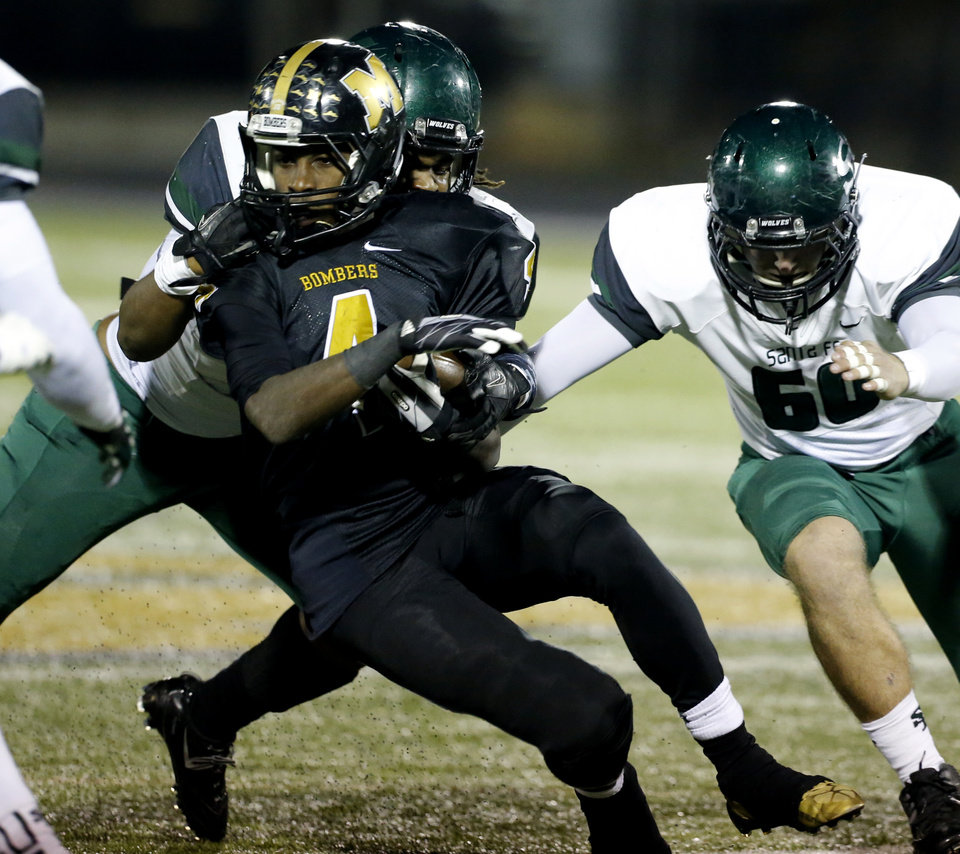 Photo - Edmond Santa Fe's Austin Mack stops Midwest City's DeSean Brown in high school football action as the Midwest City Bombers play the Edmond Santa Fe Wolves on Friday, Nov. 15, 2013  in Midwest City, Okla.  At right is Hayden Bell.  Photo by Steve Sisney, The Oklahoman