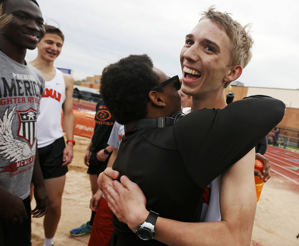 Photo - Norman's Patrick Ahearn, right, gets a hug from teammate Imond Robinson after Ahearn ran the 400-meter dash with his prosthetic leg during a track meet at Putnam City High School in Oklahoma City, Friday, April 5, 2013. Ahearn lost part of his leg in a personal watercraft accident last year. Photo by Nate Billings, The Oklahoman
