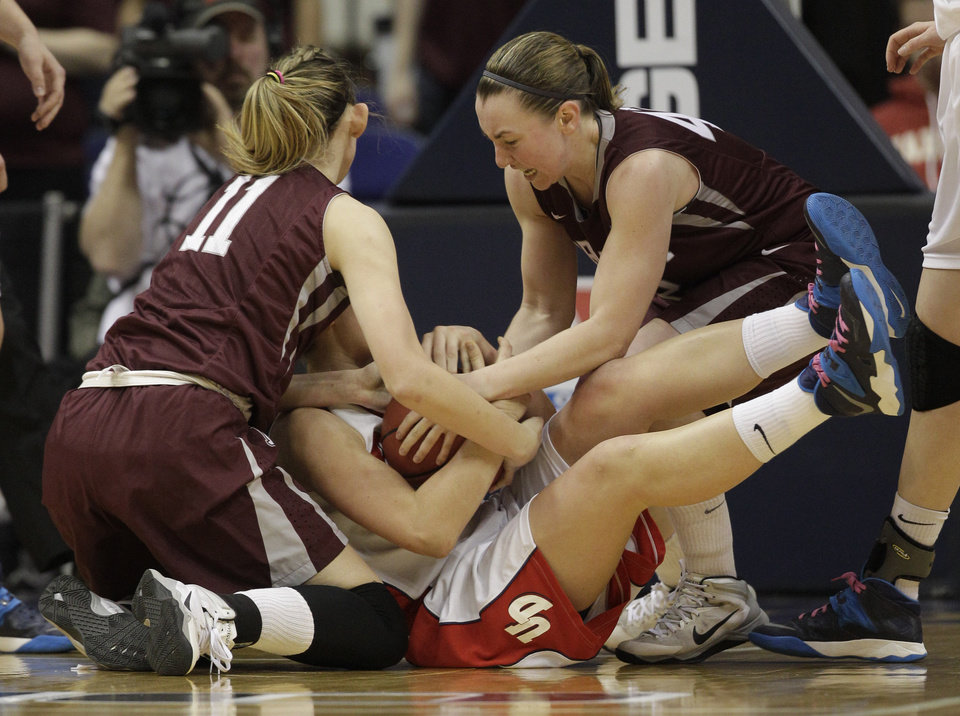 Photo - Dayton guard Andrea Hoover, center, is double-teamed by Fordham forward Emily Tapio (11) and Abigail Corning, right,  during the second half of the A10 women's basketball championship game in Richmond, Va., Sunday, March 9, 2014. Fordham defeated Dayton 63-51. (AP Photo/Steve Helber)