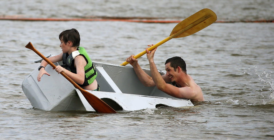 Photo -  Nathaniel Stephenson, right, and his son, Maverick, 10, try to keep Hope it Floats afloat. PHOTO BY BRYAN TERRY, THE OKLAHOMAN   Bryan Terry -  THE OKLAHOMAN