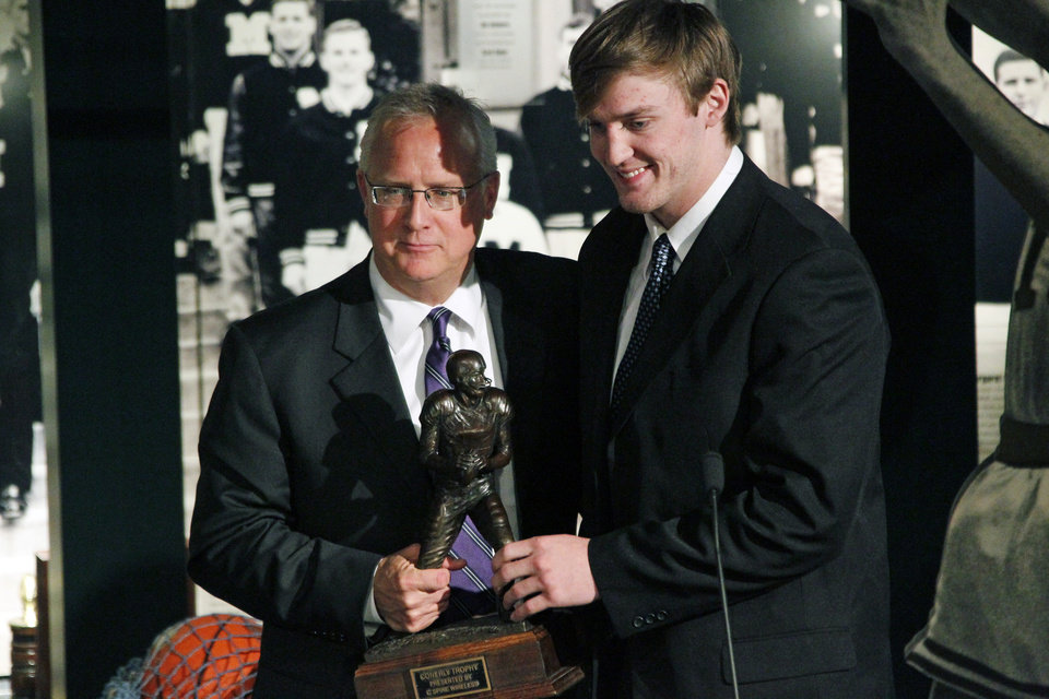 Jim Richmond, director of corporate communications at C Spire Wireless, left, poses with Mississippi quarterback Bo Wallace as they hold the Conerly Trophy, an award given annually to Mississippi\'s top NCAA college football player, Tuesday, Nov. 27, 2012, during a ceremony in Jackson, Miss. Wallace became the second straight quarterback to win the award. (AP Photo/Rogelio V. Solis)