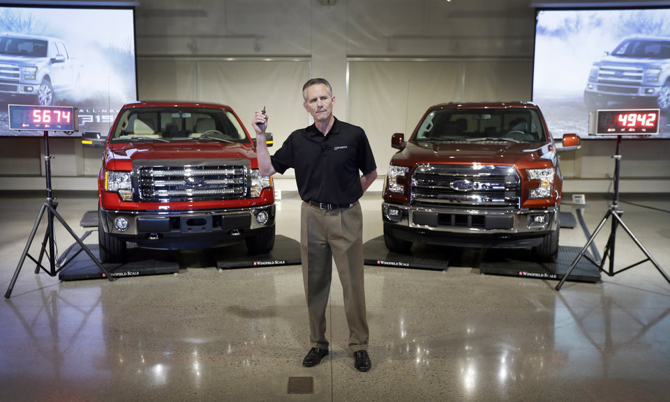 Photo - Ford Truck Group Marketing Manager Doug Scott stands between a Ford F-150 truck, left, and the new aluminum-sided 2015 F-150 truck, right, both on scales, at the company's Development Center in Dearborn, Mich., Tuesday, July 22, 2014. The weight difference between the two vehicles is 732 pounds. Ford said its new pickup can keep up with rivals despite its lighter weight. (AP Photo)