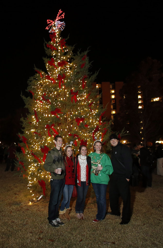 Students pose for photographs beside the newly lit Christmas Tree at the University of Oklahoma's (OU) Holiday Lighting Celebration on Wednesday, Nov. 28, 2012, in Norman, Okla.  