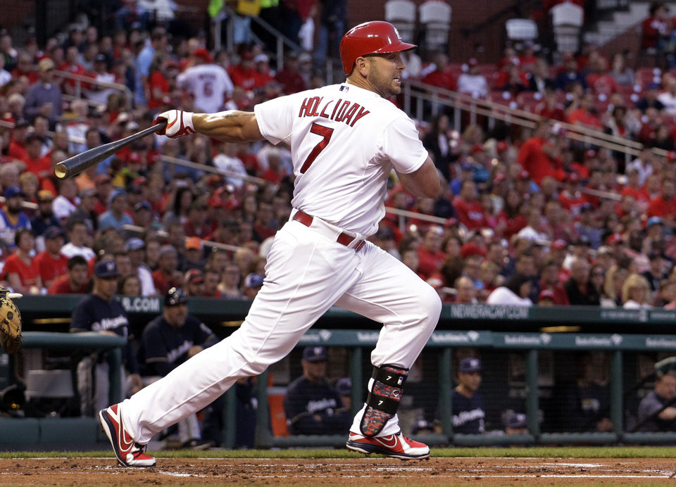 Photo - St. Louis Cardinals' Matt Holliday follows through on an RBI single during the first inning of a baseball game against the Milwaukee Brewers on Monday, April 28, 2014, in St. Louis. (AP Photo/Jeff Roberson)