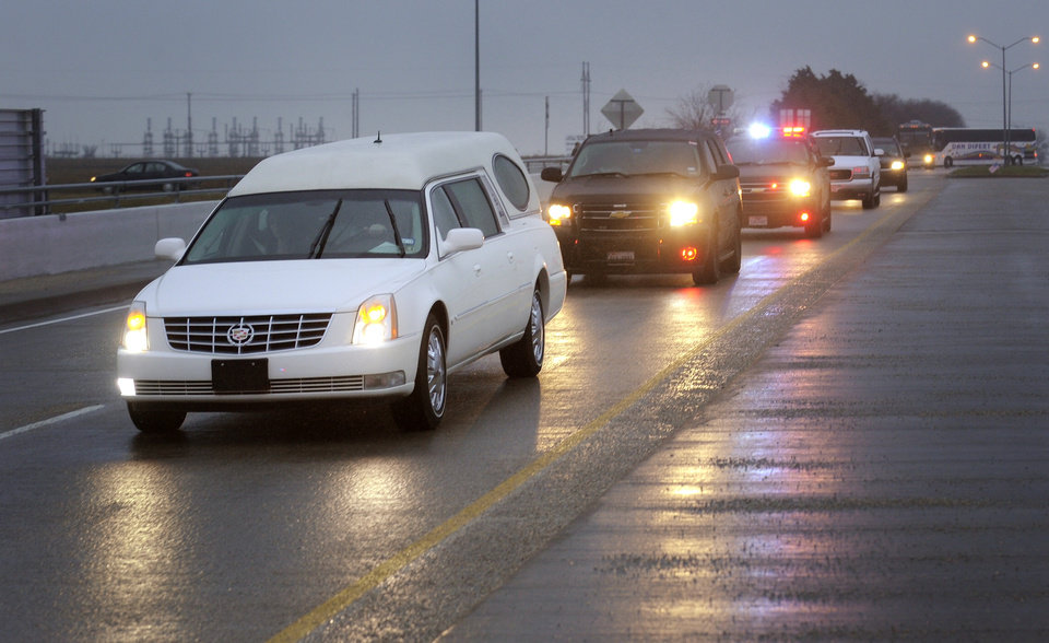 Photo - A hearse containing Chris Kyle's casket leads a motorcade leaving the Multi-Purpose Stadium, in Midlothian, Texas, Tuesday, Feb. 12, 2013 for the 200-mile journey to Austin, where Kyle will be buried at the Texas State Cemetery. Some 7,000 people attended a two-hour memorial service for Kyle at Cowboys Stadium in Arlington on Monday. Kyle and his friend Chad Littlefield were shot and killed Feb 2. at a North Texas gun range. (AP Photo/Star-Telegram, Max Faulkner)