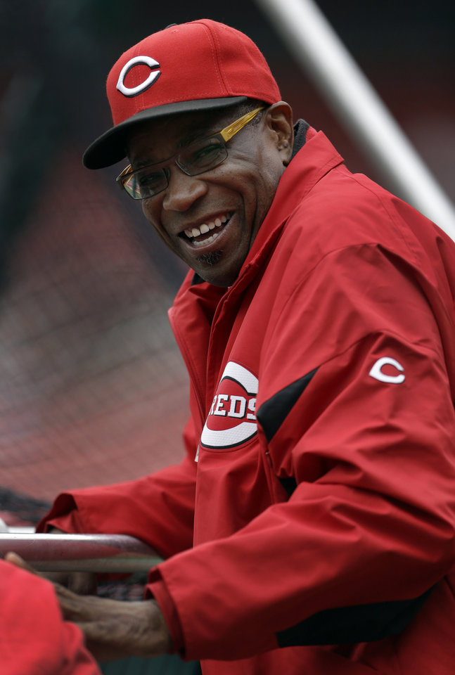 Photo -   Cincinnati Reds manager Dusty Baker smiles as he watches batting practice before a baseball game against the St. Louis Cardinals, Monday, Oct. 1, 2012, in St. Louis. Baker is back with his team after missing 11 games because of a mini-stroke, and will manage the team during the final series of the regular season. (AP Photo/Jeff Roberson)