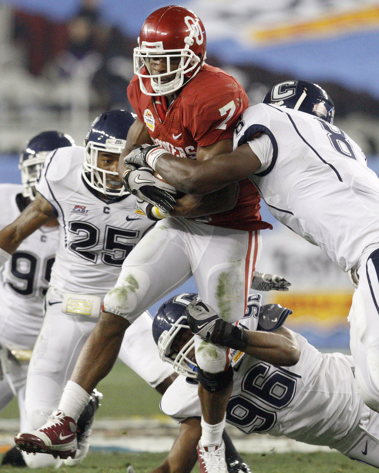 Oklahoma's Demarco Murray (7) fights off Connecticut's Harris Agbor (25), Connecticut's A.J. Portee (96), and Connecticut's Lawrence Wilson (8)during the Fiesta Bowl college football game between the University of Oklahoma Sooners and the University of Connecticut Huskies in Glendale, Ariz., at the University of Phoenix Stadium on Saturday, Jan. 1, 2011.  Photo by Bryan Terry, The Oklahoman