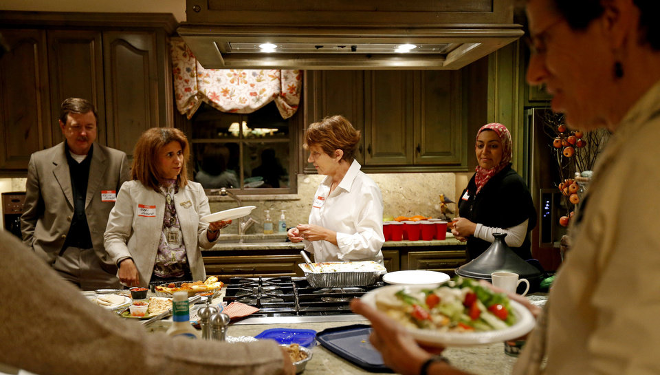 Photo - Marilyn Baragree, center, talks with Keith and Terri Angier, at left, as Sarah Albahadily, at right, looks on during a recent Amazing Faiths interfaith dinner in the Edmond area. Photo by Bryan Terry, The Oklahoman   BRYAN TERRY - THE OKLAHOMAN