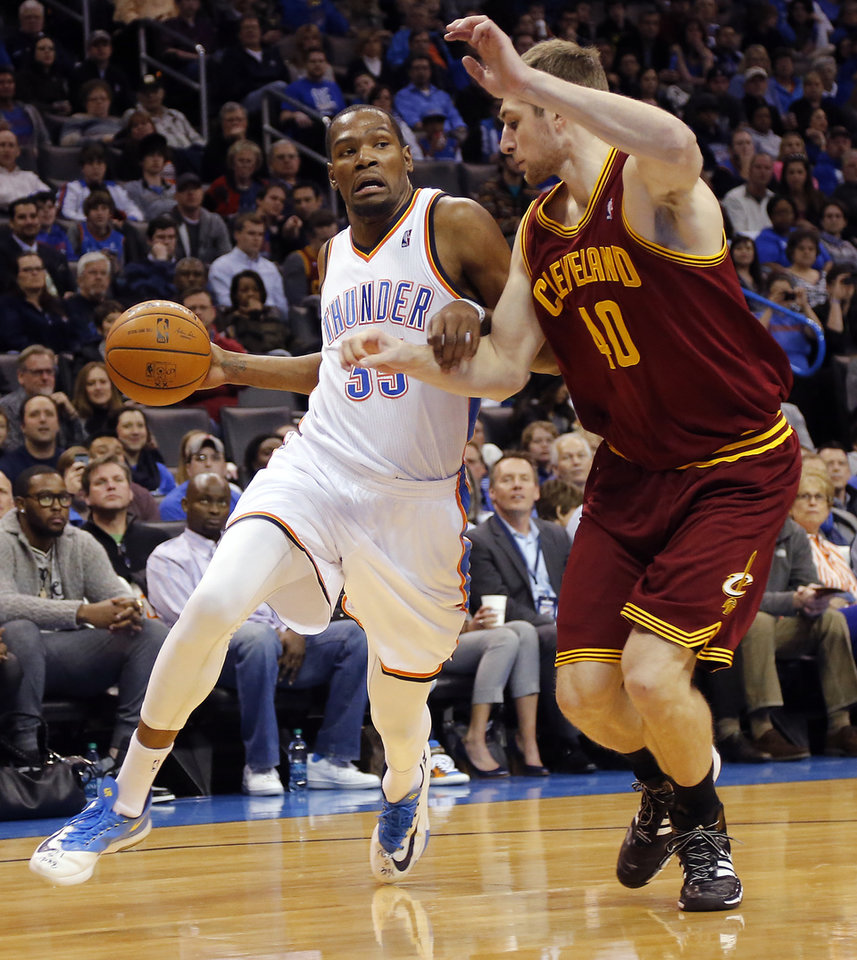 Photo - Oklahoma City's Kevin Durant (35) drives past Cleveland's Tyler Zeller (40) during the NBA basketball game between the Oklahoma City Thunder and the Cleveland Cavaliers at the Chesapeake Energy Arena in Oklahoma City, Okla. on Wednesday, Feb. 26, 2014.  Photo by Chris Landsberger, The Oklahoman