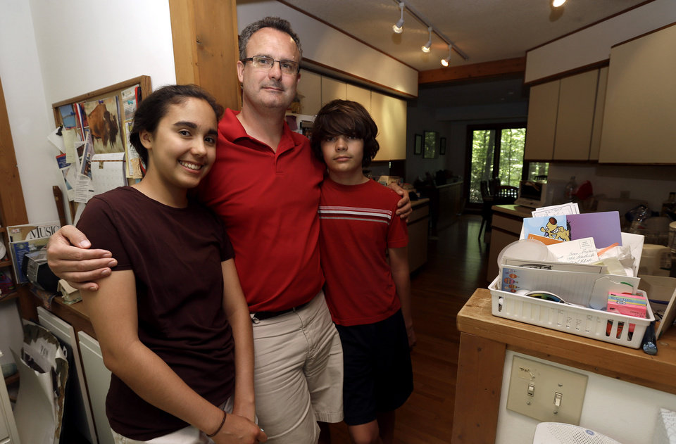 In this Friday, June 14, 2013 photo, Karl Owen poses with his children, Jordan, 15,  left, and Marcus, 13, in their Chapel Hill, N.C. home. Owen lost his wife and the mother of their two children to cancer three years ago. (AP Photo/Gerry Broome)