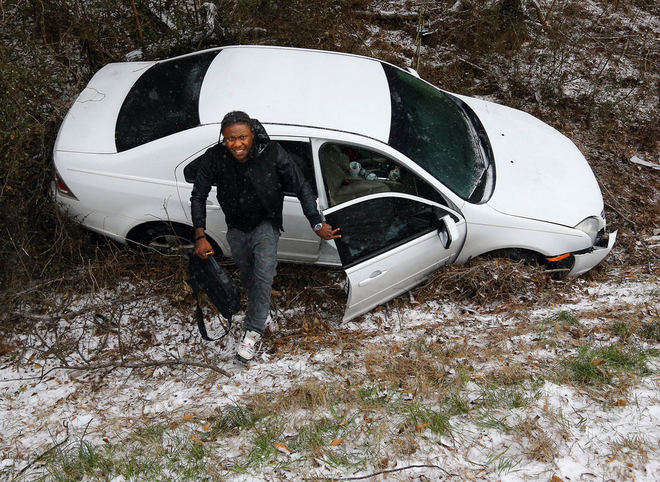 Photo - Jesse Hatcher limps away from his crash after he says another motorist caused him to lose control of his car and spin out off I-20 West near Conyers on Tuesday, Jan. 28, 2014, in Conyers, Georgia.   (AP Photo/Atlanta Journal-Constitution, Curtis Compton)
