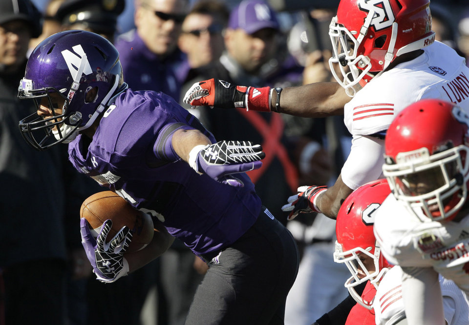 Photo -   Northwestern wide receiver Tony Jones, left, runs past South Dakota defensive back Chris Lundy (24) during the first half of an NCAA college football game in Evanston, Ill., Saturday, Sept. 22, 2012. (AP Photo/Nam Y. Huh)