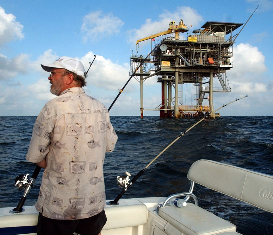 Photo - FILE - In a  in this Friday, May 9, 2003 file photo, angler Andy Hails, of Montgomery, Ala., checks the fishing lines on his boat as he trolls the Gulf of Mexico near a natural gas well off the Alabama coast near Gulf Shores, Ala. President Obama announced his new offshore drilling policy Wednesday, March 31, 2010. President Obama is allowing oil drilling off Virginia's shorelines and considering it for a large chunk of the Atlantic seaboard. At the same time, he's rejecting some new drilling sites that had been planned in Alaska.   (AP Photo/Dave Martin, File) ORG XMIT: NY117