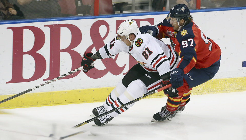Photo - Chicago Blackhawks' Marian Hossa (81) and Florida Panthers' Matt Gilroy (97) chase the puck during the second period of an NHL hockey game in Sunrise, Fla., Tuesday, Oct. 22, 2013. (AP Photo/J Pat Carter)