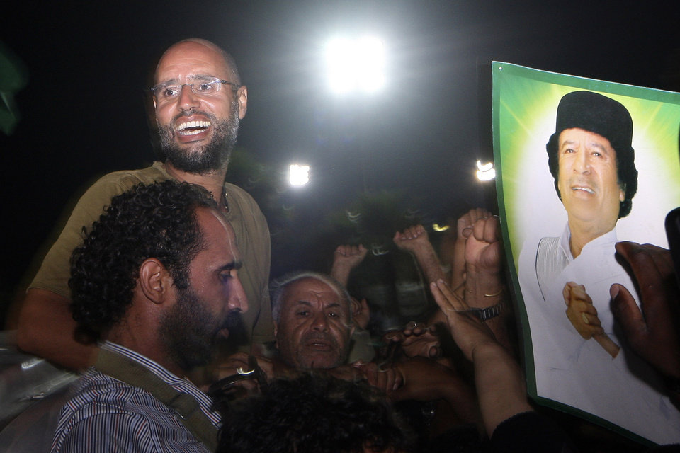 Photo -   Moammar Gadhafi's son, Seif al-Islam, top left, gestures to troops loyal to his father in Tripoli, Libya, Tuesday, Aug. 23, 2011. Seif al-Islam, who was earlier reported arrested by Libya's rebels, turned up early Tuesday morning at the hotel where foreign journalists stay in Tripoli, then took reporters in his convoy on a drive through the city. (AP Photo/Imed Lamloum, Pool)