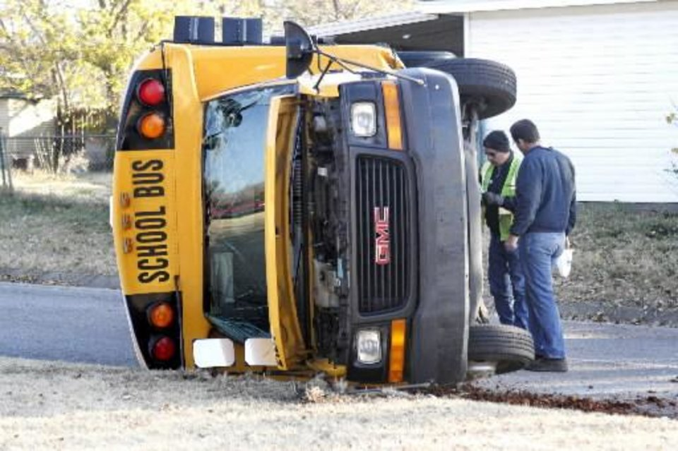 Photo - Emergency workers investigate an accident involving a school bus and an automobile at the intersection of NW 89th and Classen in Oklahoma City, OK, Tuesday, November 27, 2012, By Paul Hellstern, The Oklahoman