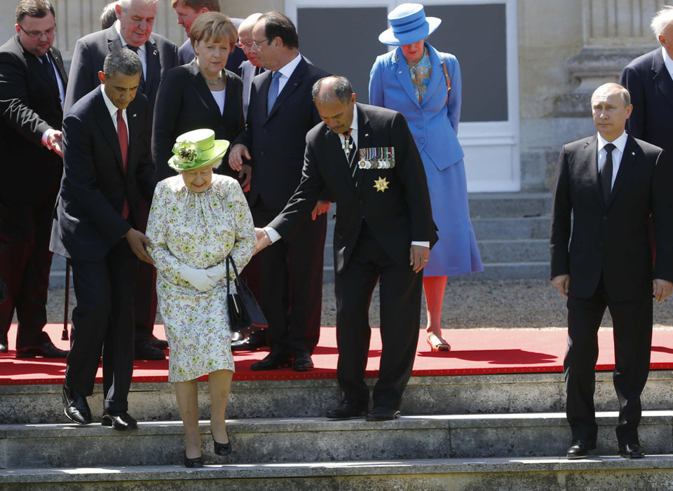 Photo - Russian President Vladimir Putin stands at right as U.S. President Barack Obama, left, and New Zealand's Governor-General Jerry Mateparae guide Britain's Queen Elizabeth II to her position for a group photo, with French President Francois Hollande, in the background, talking with German Chancellor Angela Merkel, as they take part in commemorations for  the 70th anniversary of the D-Day landings,  in Benouville in Normandy, France, Friday, June 6, 2014. (AP Photo/Charles Dharapak)