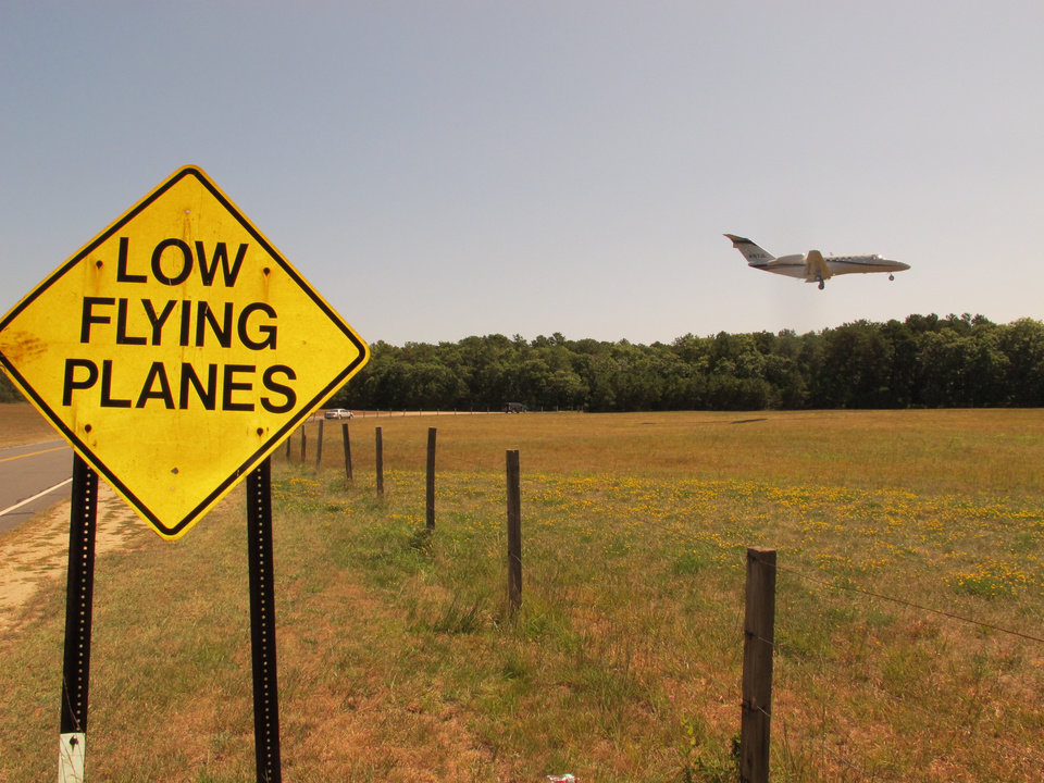 Photo - In this Wednesday, Aug. 20, 2014 photo, a small jet approaches the runway at East Hampton Town Airport. Residents across eastern Long Island are complaining about the noise generated from jets, helicopters and other aircraft that land at the small municipal airport, which is situated in the heart of the summer playground for the rich and famous. (AP Photo/Frank Eltman)