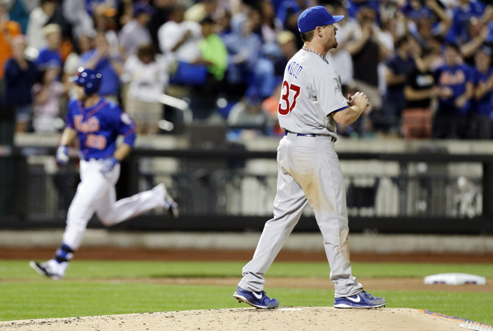 Photo - Chicago Cubs starting pitcher Travis Wood (37) reacts as New York Mets' Eric Campbell runs to home plate after hitting a three-run home run during the fourth inning of a baseball game Friday, Aug. 15, 2014, in New York. (AP Photo/Frank Franklin II)
