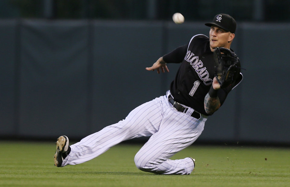 Photo - Colorado Rockies right fielder Brandon Barnes catches a fly ball by Miami Marlins' Casey McGehee in the fifth inning of a baseball game in Denver on Saturday, Aug. 23, 2014..(AP Photo/David Zalubowski)