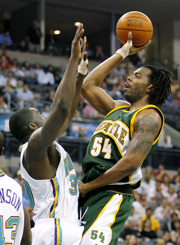 Photo - Seattle SuperSonics center Chris Wilcox (54) shoots the ball over New Orleans/Oklahoma City Hornets forward Brandon Bass, left, in the first half of an NBA basketball game Wednesday, April 12, 2006, in Oklahoma City. (AP Photo/Ty Russell)