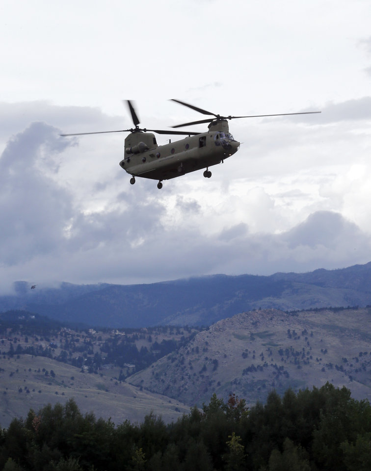 Photo - A military helicopter lands at Boulder City Airport on Friday, Sept. 13, 2013., after rescuing people from Jamestown, Colo., where they had been trapped with other towns people since Wednesday because of flooding in the mountains. (AP Photo/Ed Andrieski)