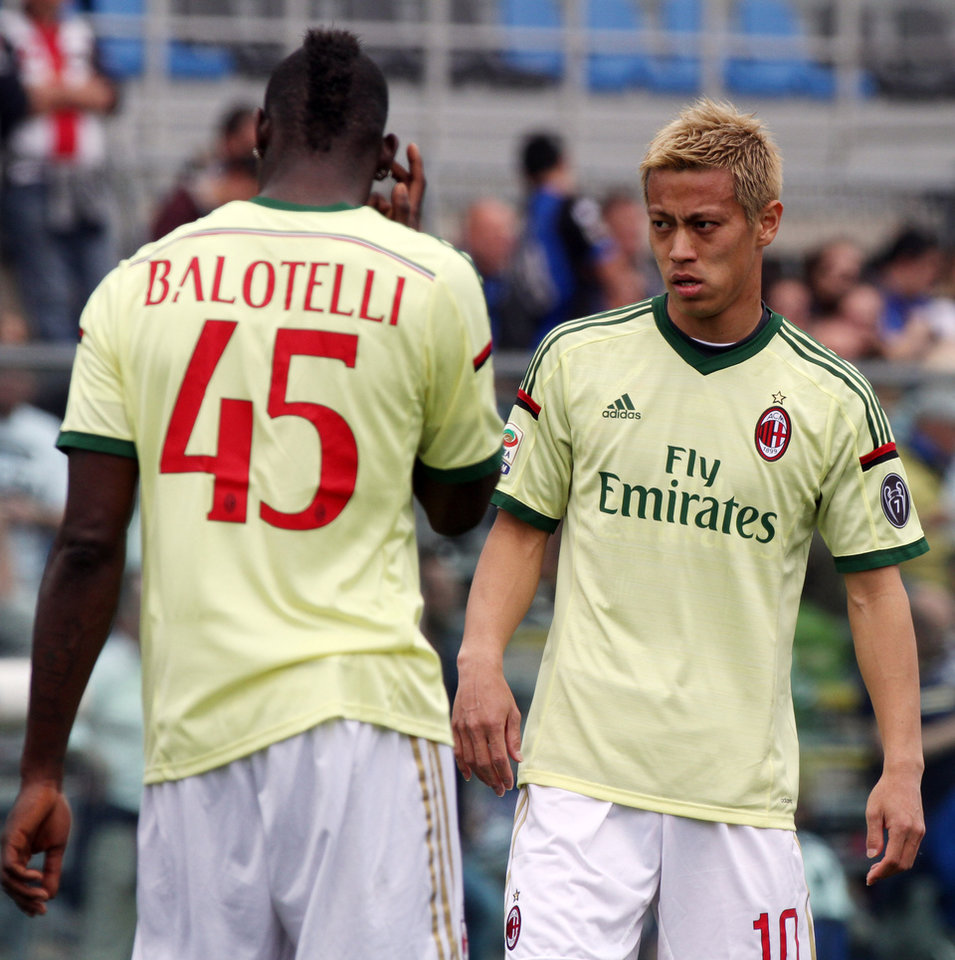 Photo - AC Milan's Keisuke Honda, right, of Japan, looks at his teammate Mario Balotelli prior to the start of a Serie A soccer match between Atalanta and AC Milan, in Bergamo, Italy, Sunday, May 11, 2014. (AP Photo/Felice Calabro')