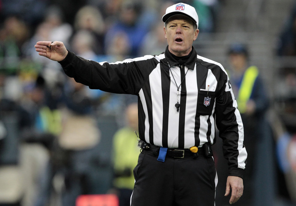 Photo -   FILE - In this Nov. 13, 2011, file photo, referee Scott Green makes a call in the second half of an NFL football game between the Seattle Seahawks and Baltimore Ravens in Seattle. The NFL and referees' union reached a tentative agreement on Wednesday, Sept. 26, 2012, to end a three-month lockout that triggered a wave of frustration and anger over replacement officials and threatened to disrupt the rest of the season. (AP Photo/Elaine Thompson, File)