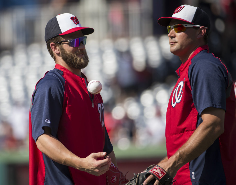 Photo - Washington Nationals outfielder Bryce Harper, left, talks with teammate Ryan Zimmerman before the start of a baseball game against the Colorado Rockies at Nationals Park, on Monday, June 30, 2014, in Washington. Harper is returning to the lineup after missing 59 games with a torn ulnar collateral ligament in his left thumb. (AP Photo/Evan Vucci)