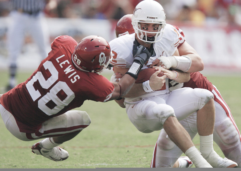 Texas' Colt McCoy, right, is brought down by Oklahoma's Travis Lewis, left, and Auston English during the second half Saturday. With middle linebacker Ryan Reynolds out for the season, the rest of the Sooner defense will have to step up.Photo by CHRIS LANDSBERGER, THE OKLAHOMAN <strong></strong>