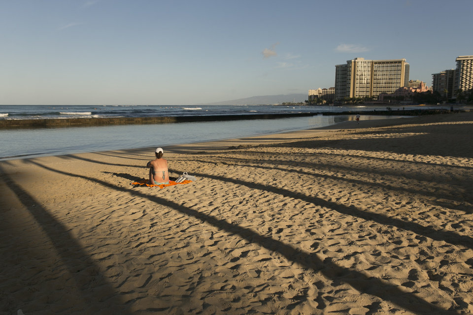 Photo - A sunbather sits on the beach in Waikiki in Honolulu on Thursday, Aug. 7, 2014. With Iselle, Hawaii is expected to take its first direct hurricane hit in 22 years. Tracking close behind it is Hurricane Julio. (AP Photo/Marco Garcia)